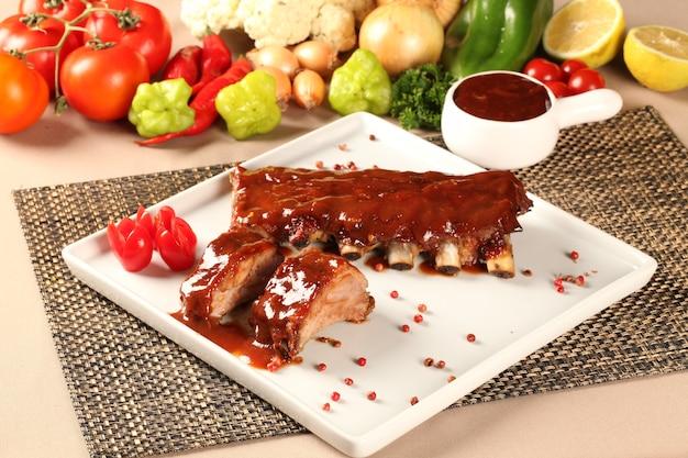 맛있는 구운 돼지 갈비가 흰 접시를 차지했습니다. 바베큐 크림.