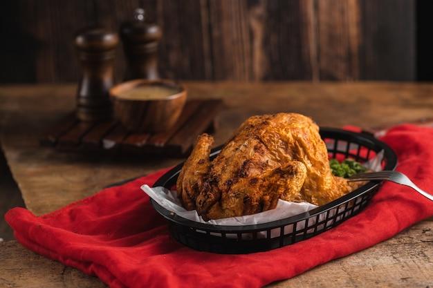 Delizioso pollo arrosto vicino ad alcune spezie su una tovaglia rossa su un tavolo di legno