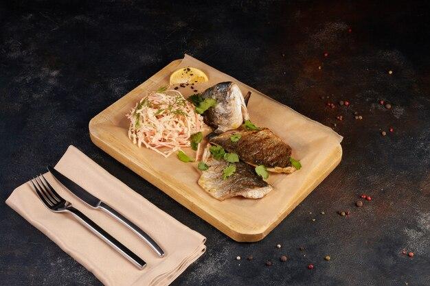 어두운 배경에 접시에 레몬 조각, 향신료, 신선한 로즈마리와 시금치와 함께 맛있는 구운 황새