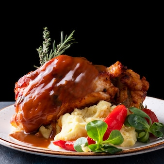 Delicious roasted pork knuckle with mashed potatoes on a plate.