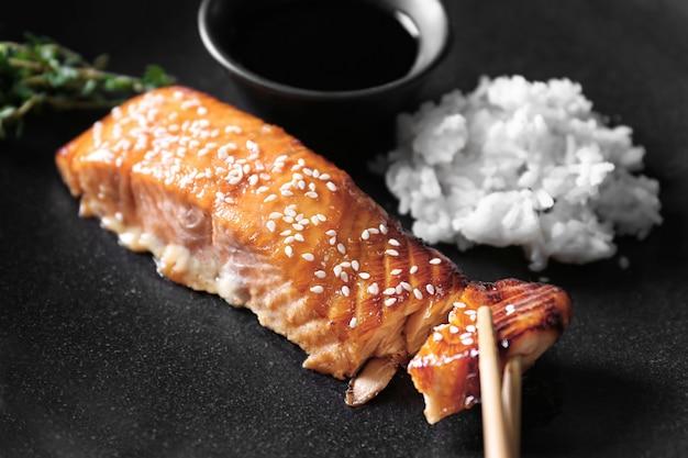Вкусное жареное филе лосося с рисом и соевым соусом на черной тарелке