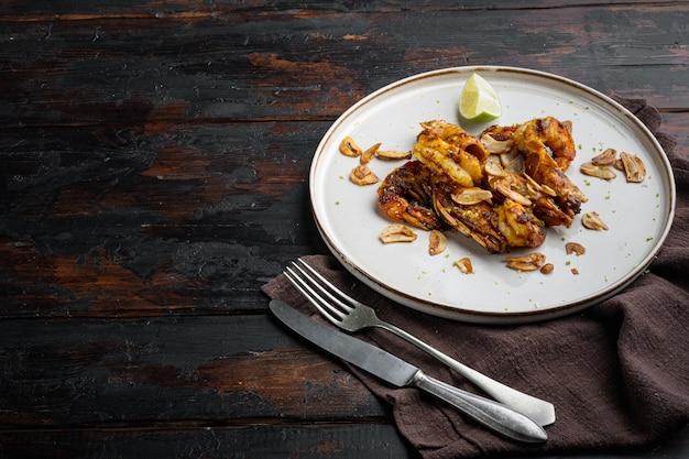 오래 된 어두운 나무 테이블에 접시에 마늘, 카레, 망고 소스 세트와 함께 맛있는 구운 새우