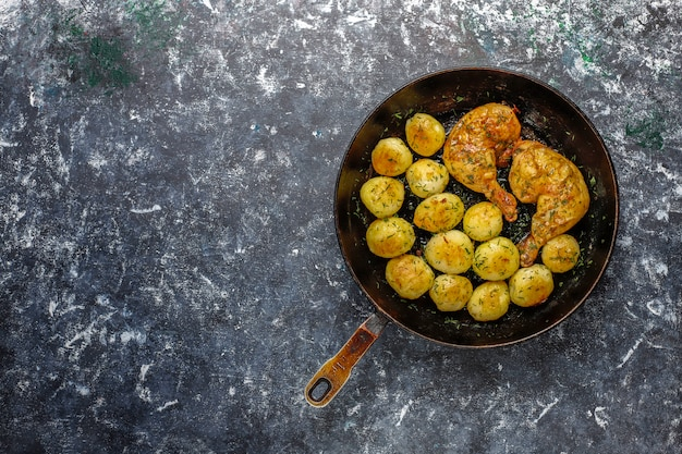 Delicious roasted young potatoes with dill and chicken, top view