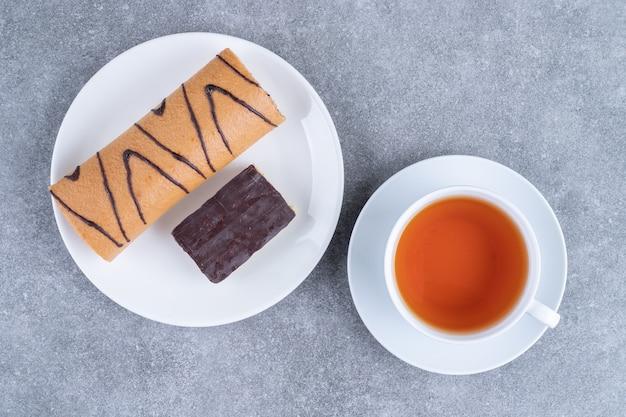 Deliziosa torta roll con cioccolato su piatto bianco e tazza di tè