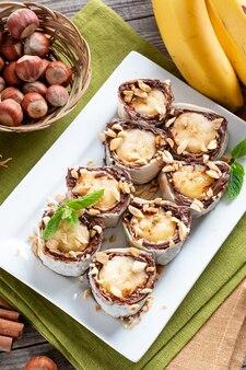 木製のテーブルにバナナのスライスとおいしいロール。バナナロールとチョコレートデザート
