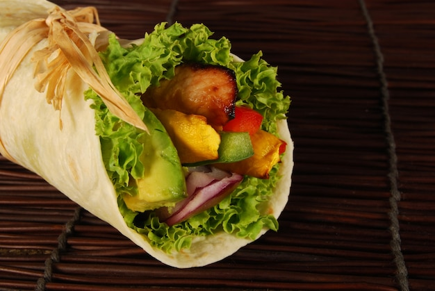 Delicious rolled sandwich with chicken and avocado