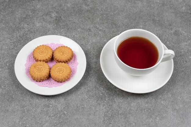 대리석 표면에 맛있는 둥근 비스킷과 차 한잔