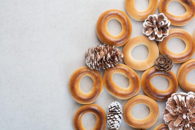白い背景の上の松ぼっくりとおいしい丸いクッキー。高品質の写真