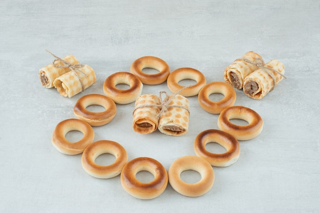 白い背景の上のロープでワッフルとおいしい丸いクッキー。高品質の写真