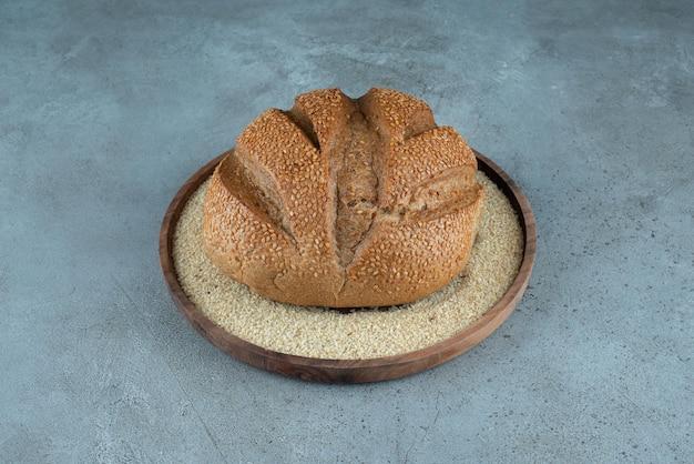 Вкусная ржаная булочка на деревянной тарелке.