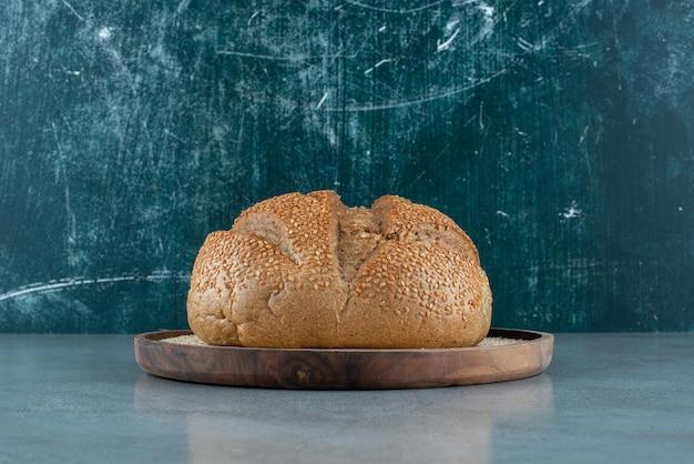 Panino di segale delizioso sul piatto di legno.