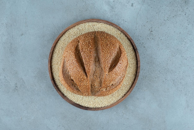 Delicious rye bun on wooden plate.