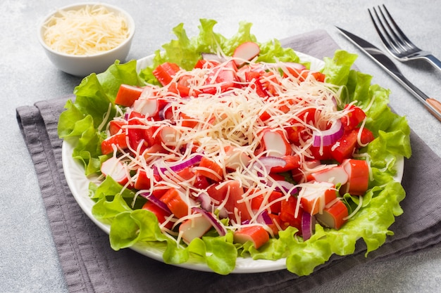A delicious salad of crab sticks cherry tomatoes and grated cheese with onions in a serving plate.