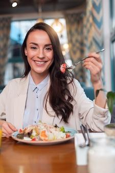 美味しいサラダ。カメラを見つめ、テーブルに座ってフォークを持ち上げる魅力的な陽気な幸せな女性