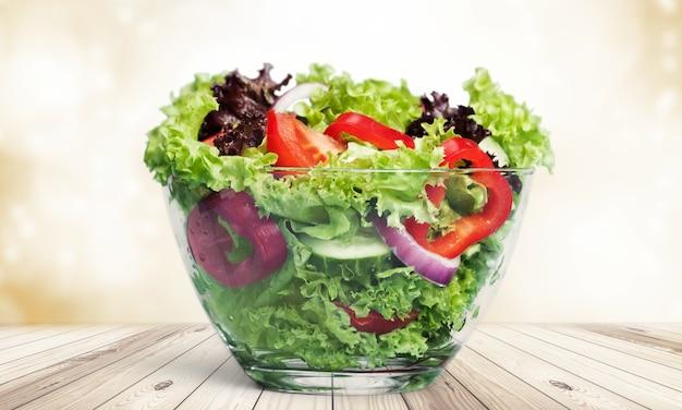 배경에 고립 된 그릇에 맛있는 샐러드