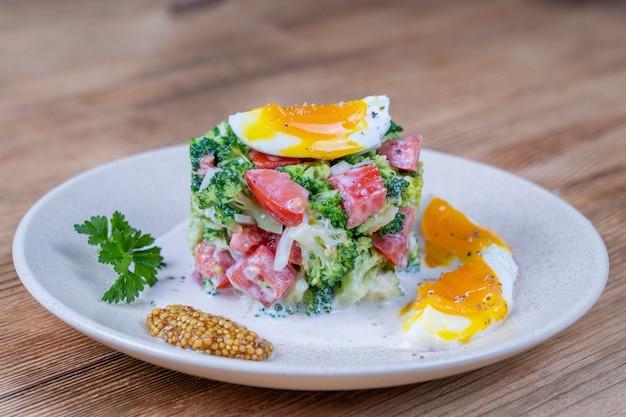 Вкусный салат с брокколи, помидорами, луком и вареным яйцом со сливочным соусом в тарелке на деревянных фоне. здоровая еда, крупным планом