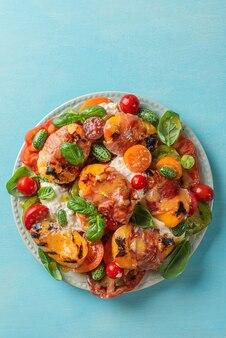Вкусный салат с сыром буррата, персиками на гриле и прошутто, сыром буррата, помидорами, огурцом, оливковым маслом и базиликом. вид сверху. здоровое диетическое питание. вертикальная ориентация
