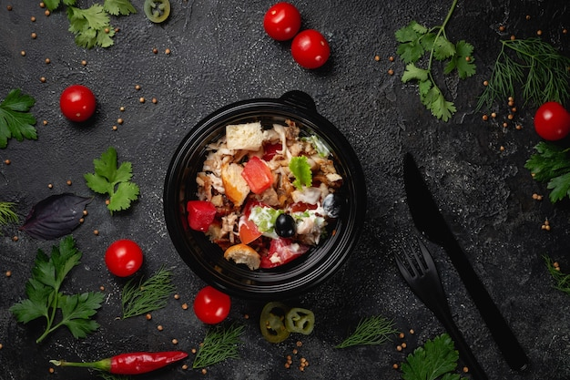 チキン、オリーブ、新鮮なハーブを使ったおいしいサラダ、ダークストーンのテーブルにあるファーストフードレストランのメニューにある新鮮なサラダ。ファーストフードの健康的なオプション。