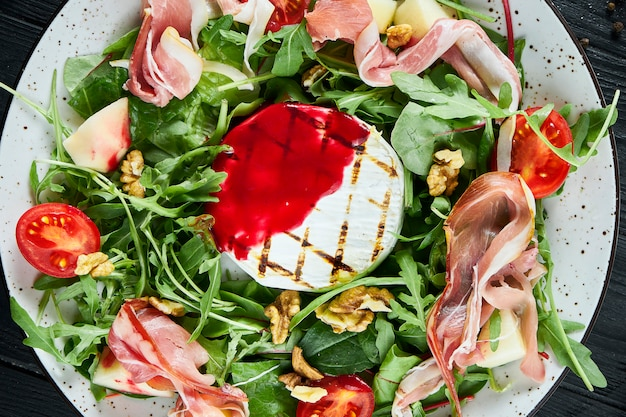 カマンベール焼き、ルッコラ、ほうれん草、ハモン、チェリートマトの黒地に白のおいしいサラダ