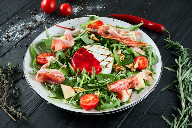 Delicious salad with grilled camembert, arugula, spinach, jamon, cherry tomatoes in white on black