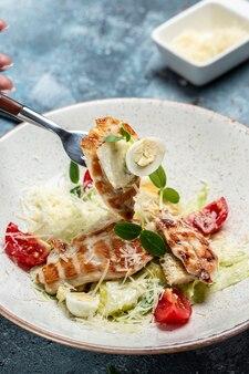 Вкусный салат с курицей гриль, сыром, перепелиными яйцами и помидорами черри, с соусом. вкусная концепция сбалансированного питания.
