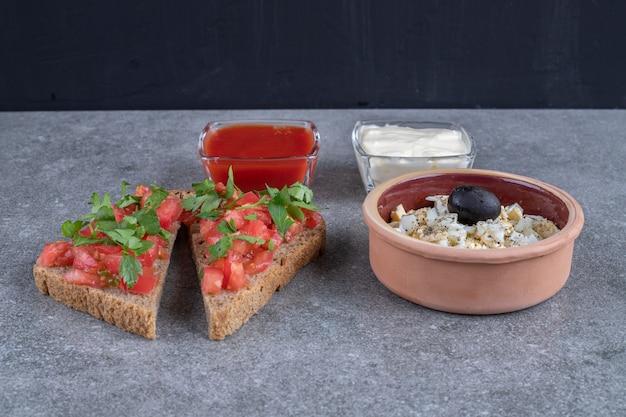 灰色の背景にマヨネーズとケチャップを添えたおいしいサラダ。高品質の写真