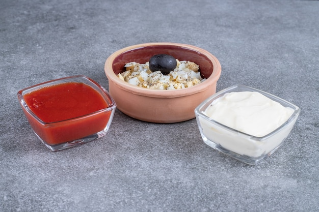 Delicious salad with mayonnaise and ketchup on a gray surface