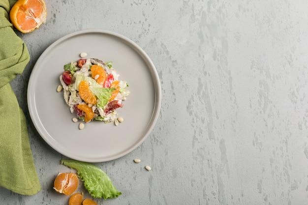 Вкусный салат с мандаринами, курицей, кедровыми орешками, листьями салата и сладким болгарским перцем, заправленный соусом цезарь