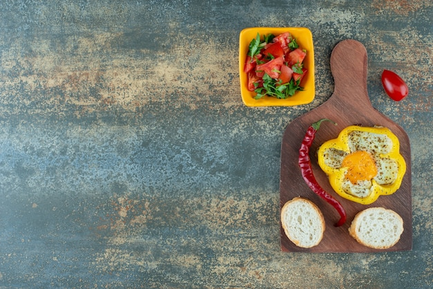 Delicious salad in yellow plate with fried omelet in pepper on marble background
