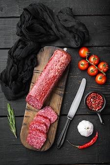 Вкусная колбаса салями со специями и розмарином, на черном деревянном столе, плоская планировка, вид сверху