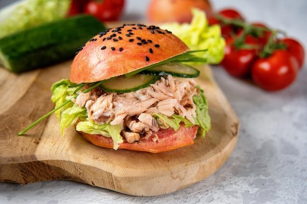 나무 보드에 분홍색 롤빵과 맛있는 연어 햄버거. 건강한 해산물 개념
