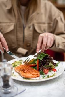 木製のテーブルの上のレストランでおいしいサーモンカフェメニューでワインとおいしいシーフード