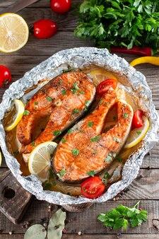 Вкусный стейк из лосося, обжаренный с лимоном и перцем на деревянном столе. источник омеги, здорового питания. вид сверху
