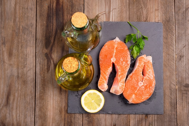 Delicious salmon steak on wooden table, top view