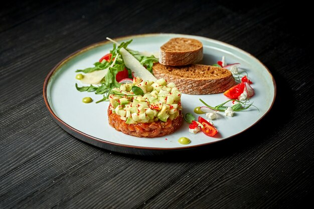 Вкусный тартар из лосося с авокадо и гренками на тарелке. деревянный фон. выборочный фокус