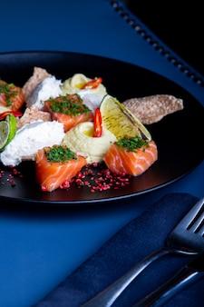 レストランでパテとフムスのおいしいサーモン。大きな黒い大皿のクローズアップで健康的な高級食品