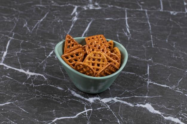 Cracker salati deliziosi in ciotola blu.