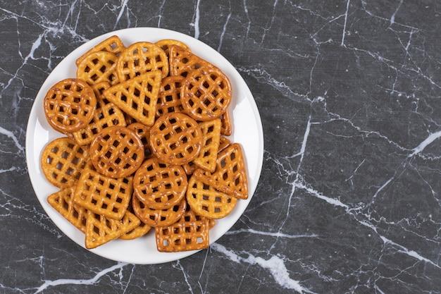 Вкусные соленые крекеры на белой тарелке.