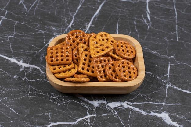 Вкусные соленые крекеры на деревянной тарелке.