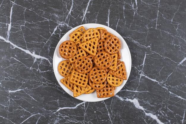 Cracker salati deliziosi sul piatto bianco.