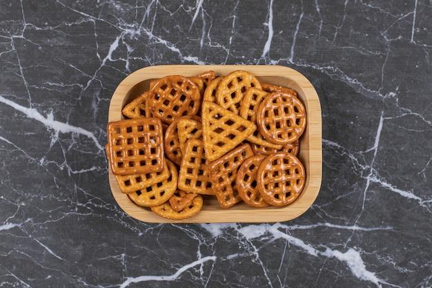 Deliziosi cracker salati sul piatto di legno.