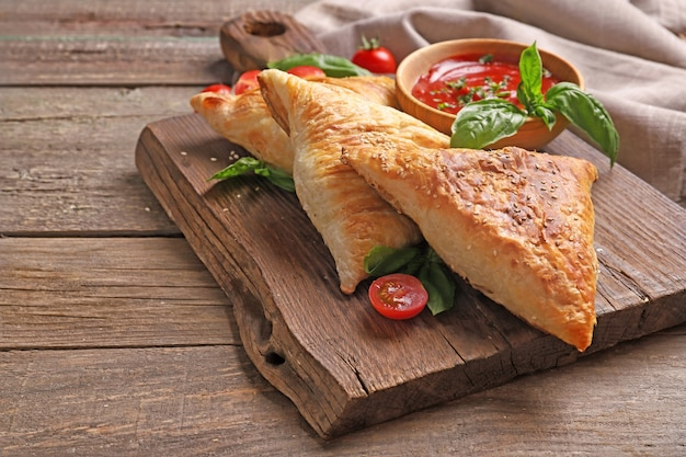 Delicious samsa with chicken meat and sauce on wooden table