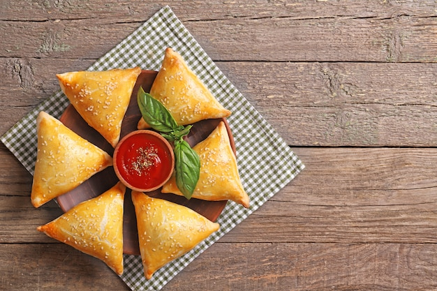Delicious samsa with sauce and basil on a wooden table. top view