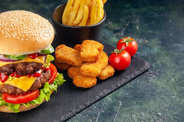 黒い表面の右側にある濃い色のトレイにおいしいサンドイッチとチキンナゲットのフライドポテト