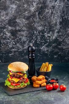おいしいサンドイッチとチキン ナゲットのフライド ポテト、暗い色のトレイ トマト、垂直ビューの黒い表面に