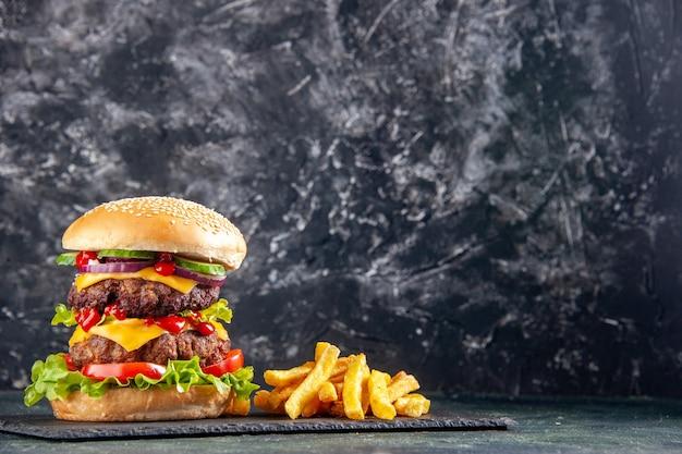 Вкусный бутерброд и картофель фри на подносе темного цвета с правой стороны на черной поверхности