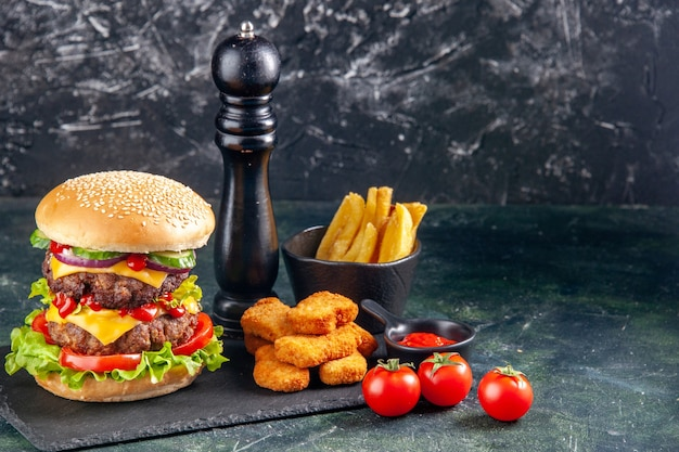 Delicious sandwich and chicken nuggets fries on dark color tray tomatoes on black surface