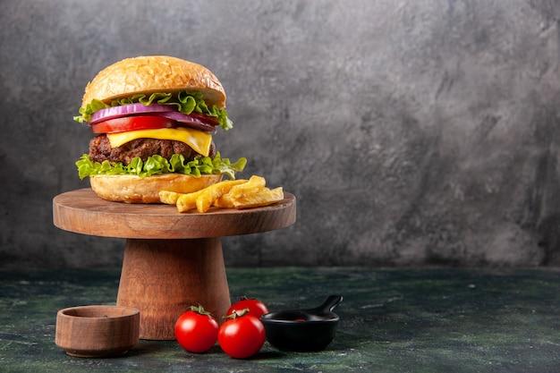 Deliziose patatine fritte su tagliere di legno pomodori ketchup pepe sul lato sinistro su superficie di colore scuro mix