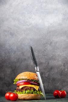 여유 공간이있는 어두운 혼합 색상 표면에 줄기 칼로 맛있는 샌드위치 토마토