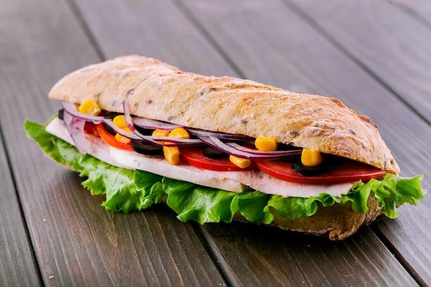 Вкусный бутерброд с синим луком, кукурузой и мясом